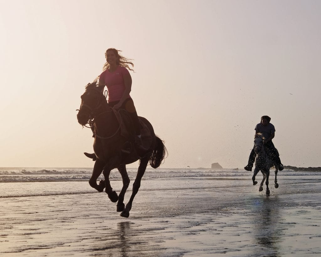 kate storm galloping on a beach while horseback riding nicaragua