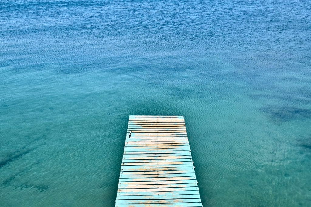 view of a dock over the water in utila honduras as seen from above. views like this don't add to the bottom line of a trip to honduras budget
