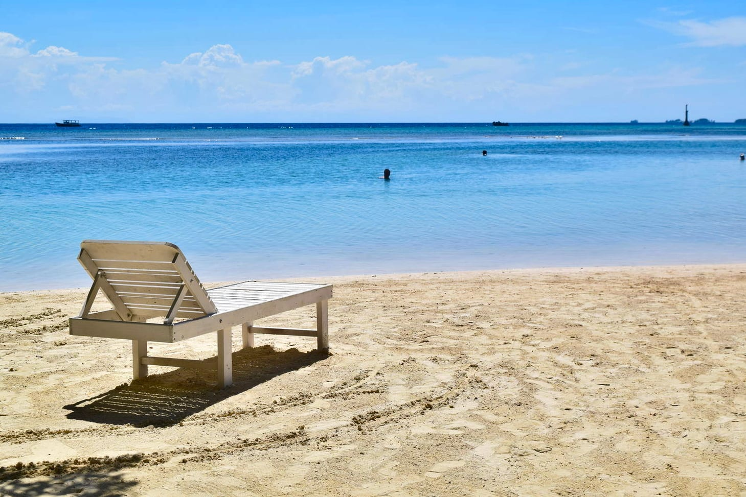 photo of a white lawn chair on a beach in utila--views like this are a very affordable part of a honduras travel budget