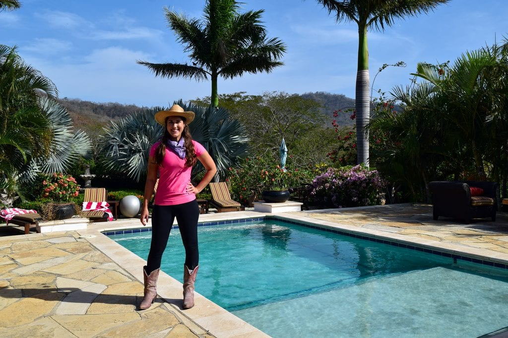 kate storm in a pink shirt dressed up for riding, standing in front of a pool