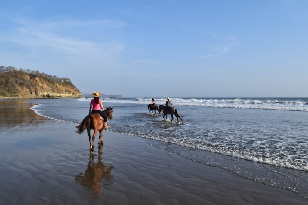 kate storm in a pink shirt horseback riding in nicaragua on a beach