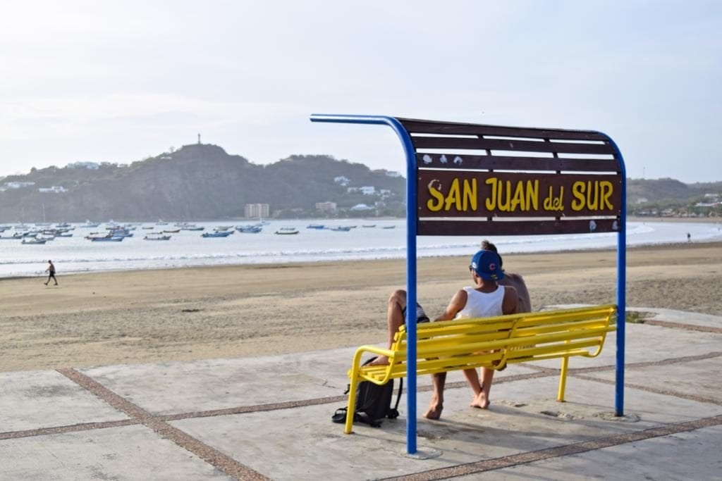 couple sitting on a yellow and blue bench in front of the san juan del sur nicaragua bench