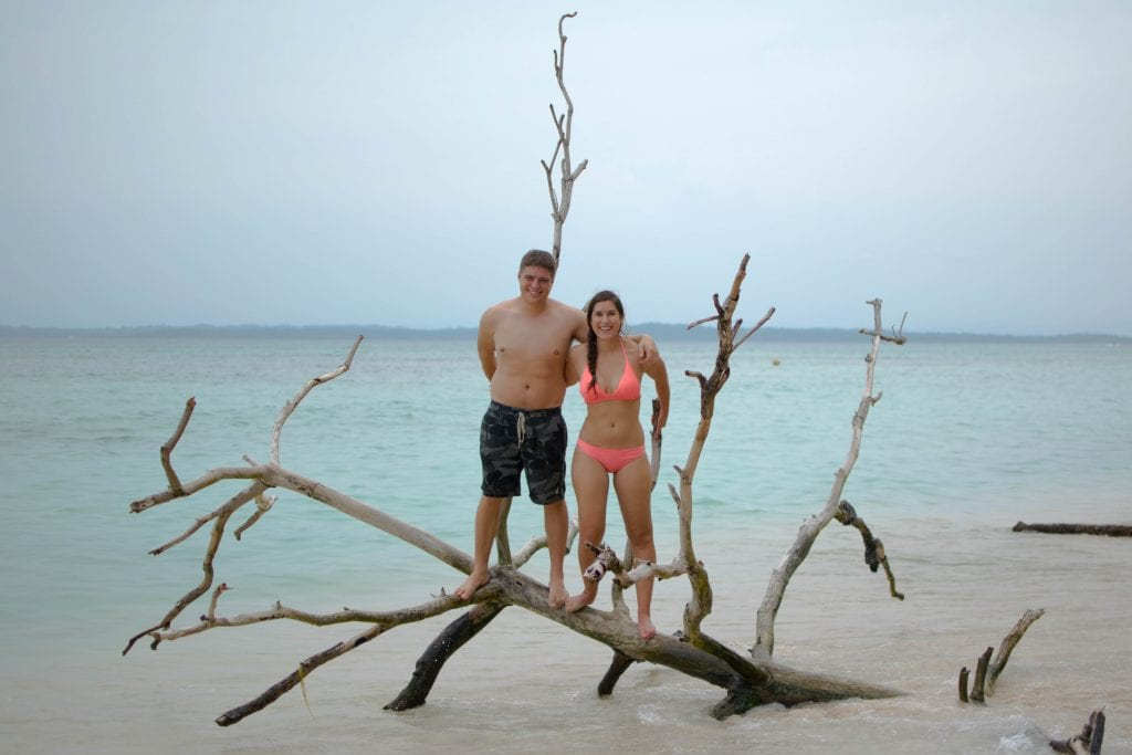 kate storm and jeremy storm standing on a branch on a cloudy beach