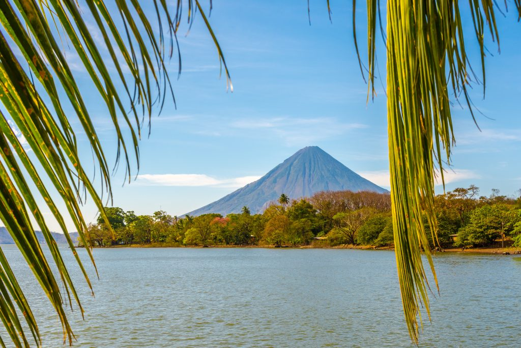 volcano concepcion in ometepe nicaragua as seen through palm leaves