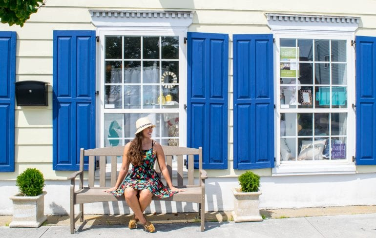 Fun Things to Do in Beaufort NC: Girl on bench in front of boutique with blue shutters