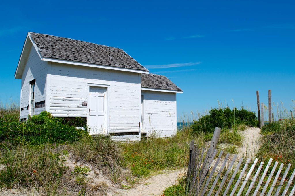 Small white outbuilding surrounded by sand dunes on Cape Lookout National Seashore