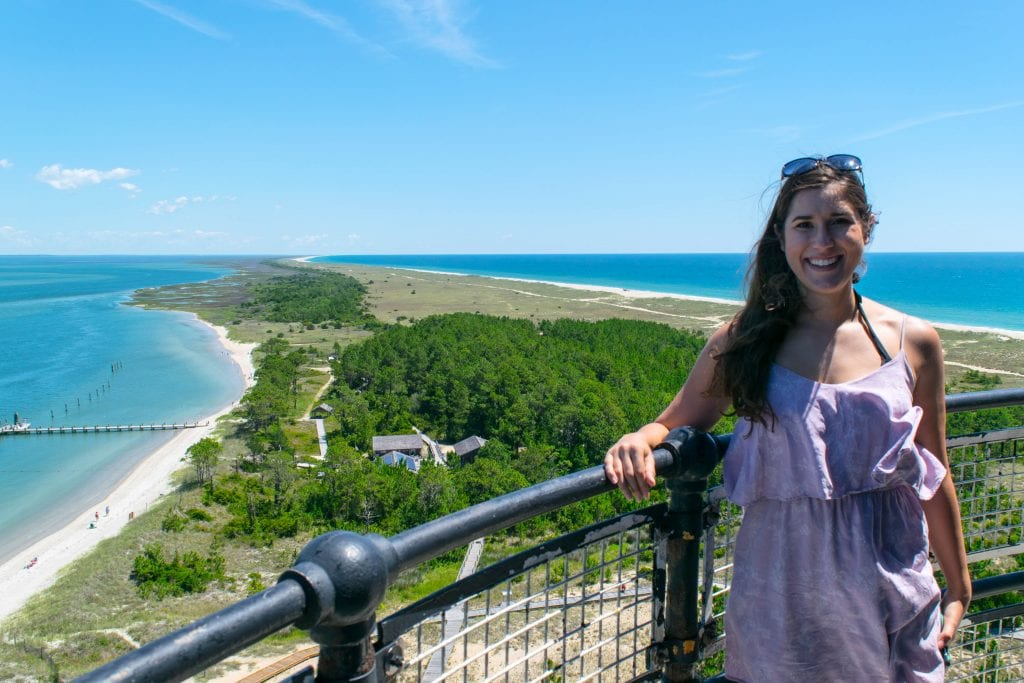 Kate Storm in a purple dress standing at the top of Cape Lookout lighthouse with the barrier island visible behind her
