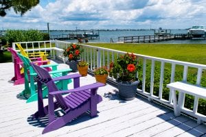 4 colorful beach chairs on a white deck overlooking the Bogue Sound in Atlantic Beach NC