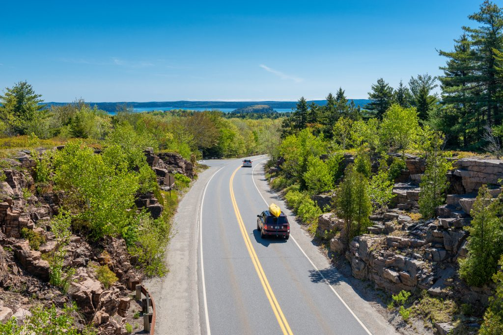 aerial view of cars driving through acadia national park in maine