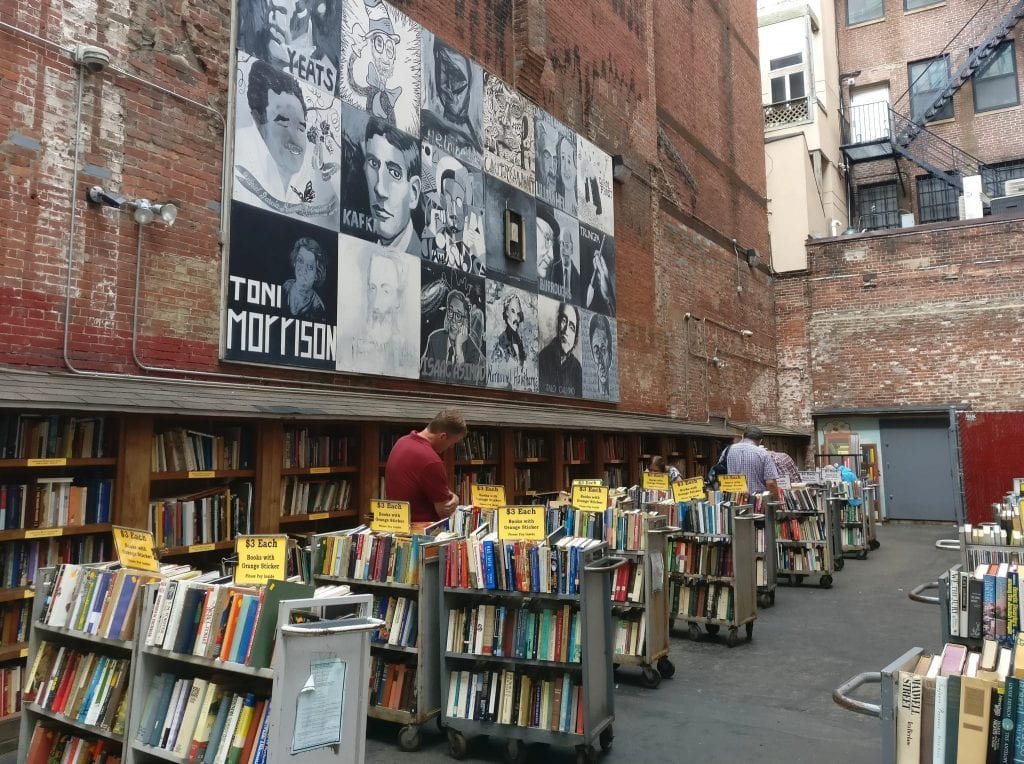 Exterior section of Brattle Bookshop in Boston MA with bookshelves and a mural nearby--one of the best things ot do in Boston MA