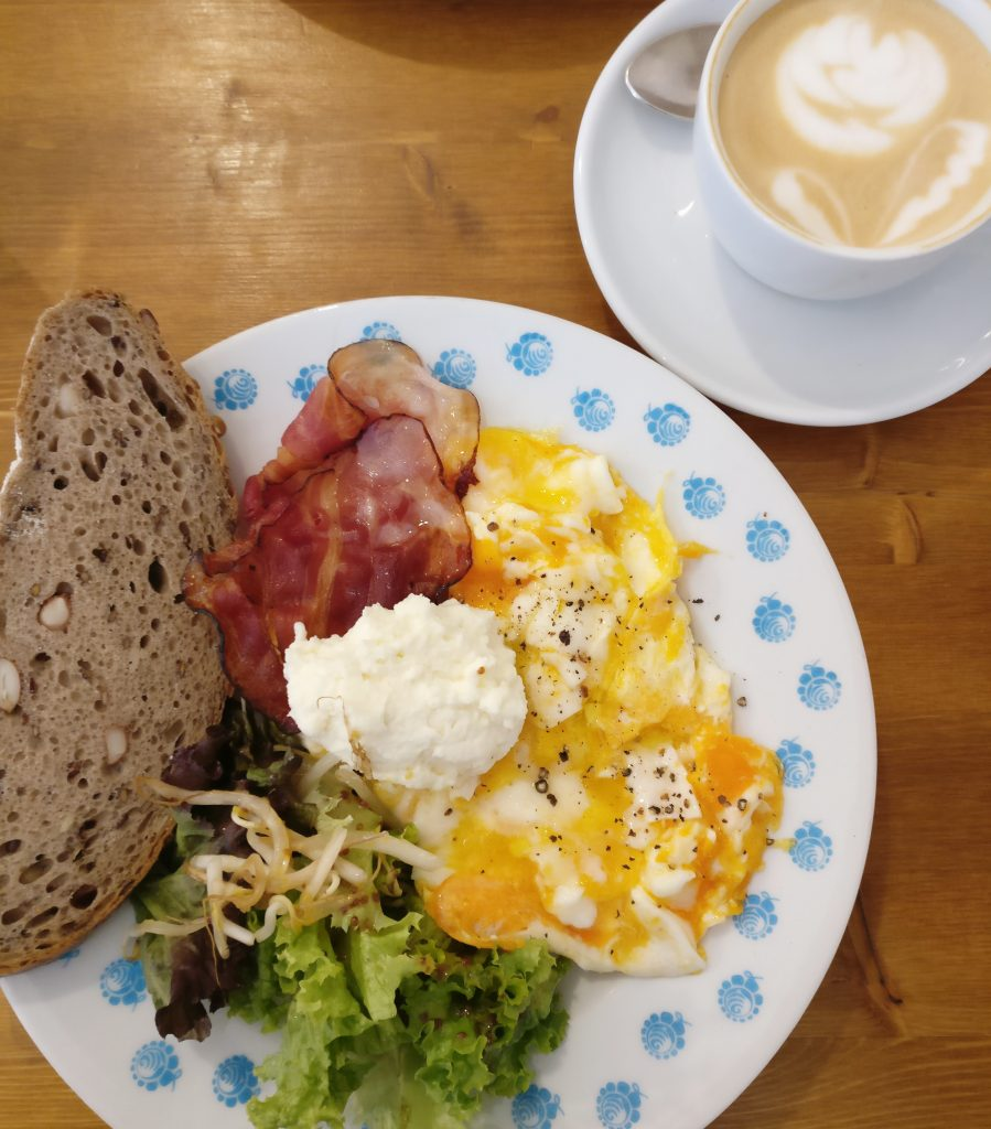 view of a scrambled egg, bacon, salad, and bread breakfast in prague with coffee shot from above