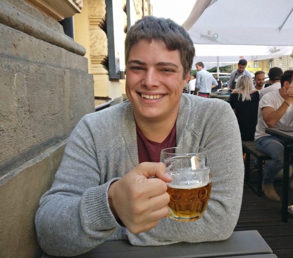 jeremy storm drinking a beer at a restaurant in prague czech republic with a gray sweater on