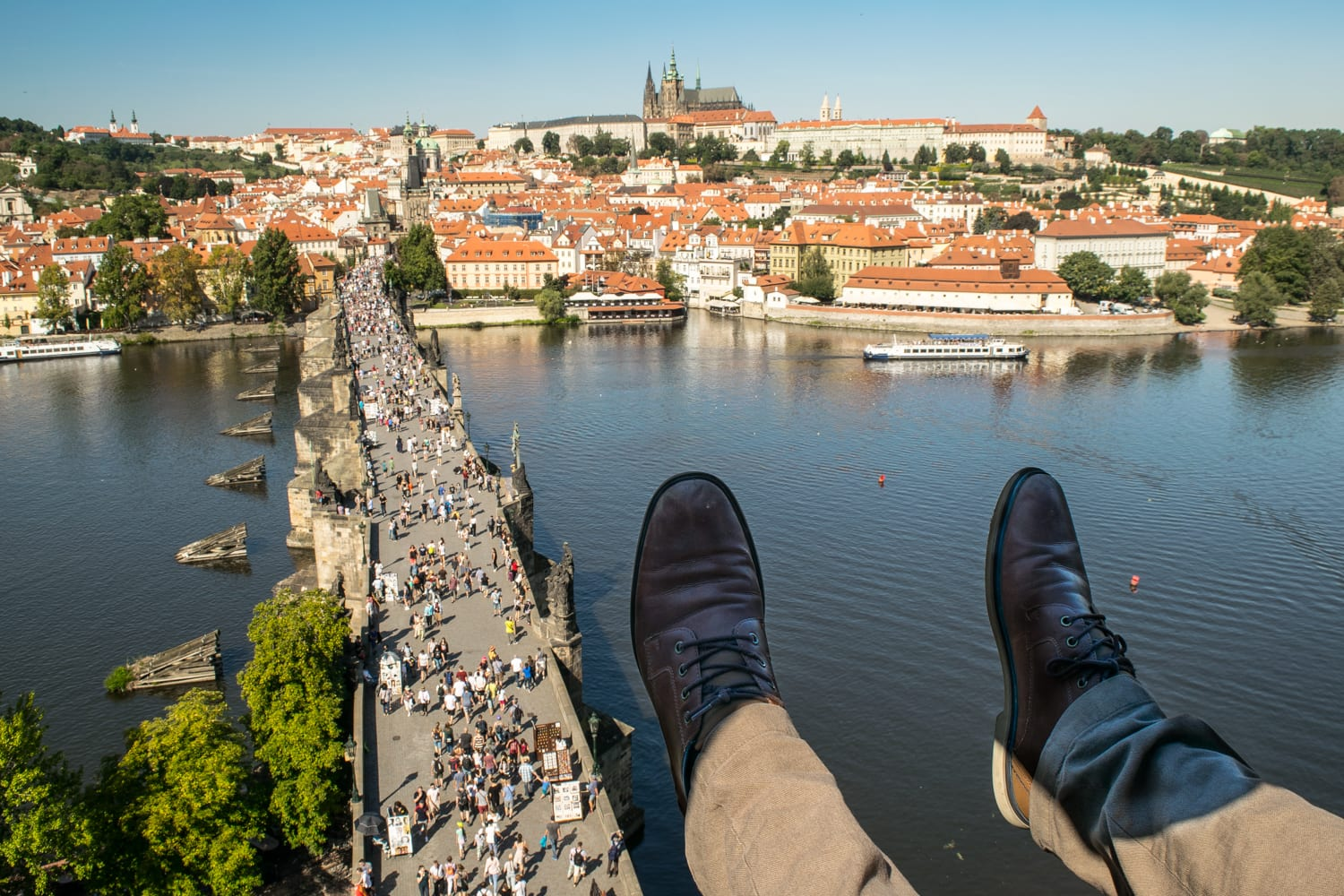jeremy storms feet overlooking charles bridge from a tower one of the best views in prague and cheap to access when traveling prague on a budget