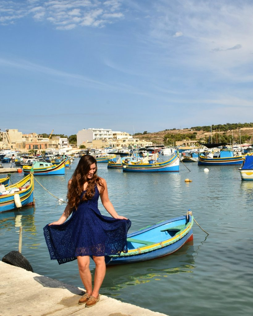 kate storm in a navy blue dress in front of the marsaxlokk harbor, one of the best places to visit in malta