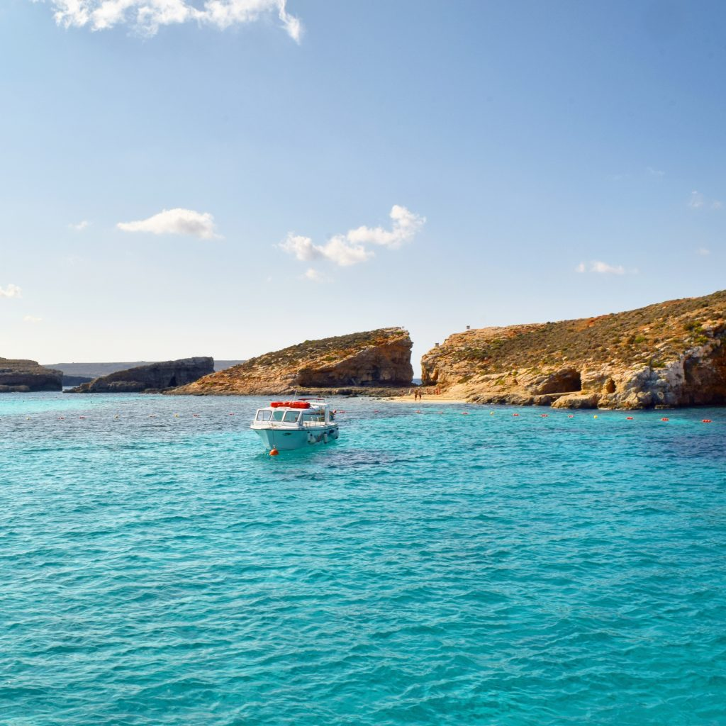 small boat in otherwise empty blue lagoon malta