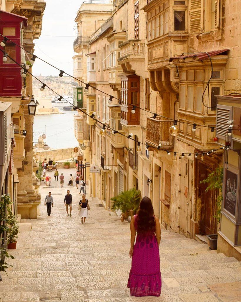 kate storm wearing a pink dress on a side street in valletta malta