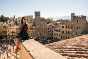 Kate Storm sitting on a ledge overlooking Arezzo, one of the best day trips from Florence