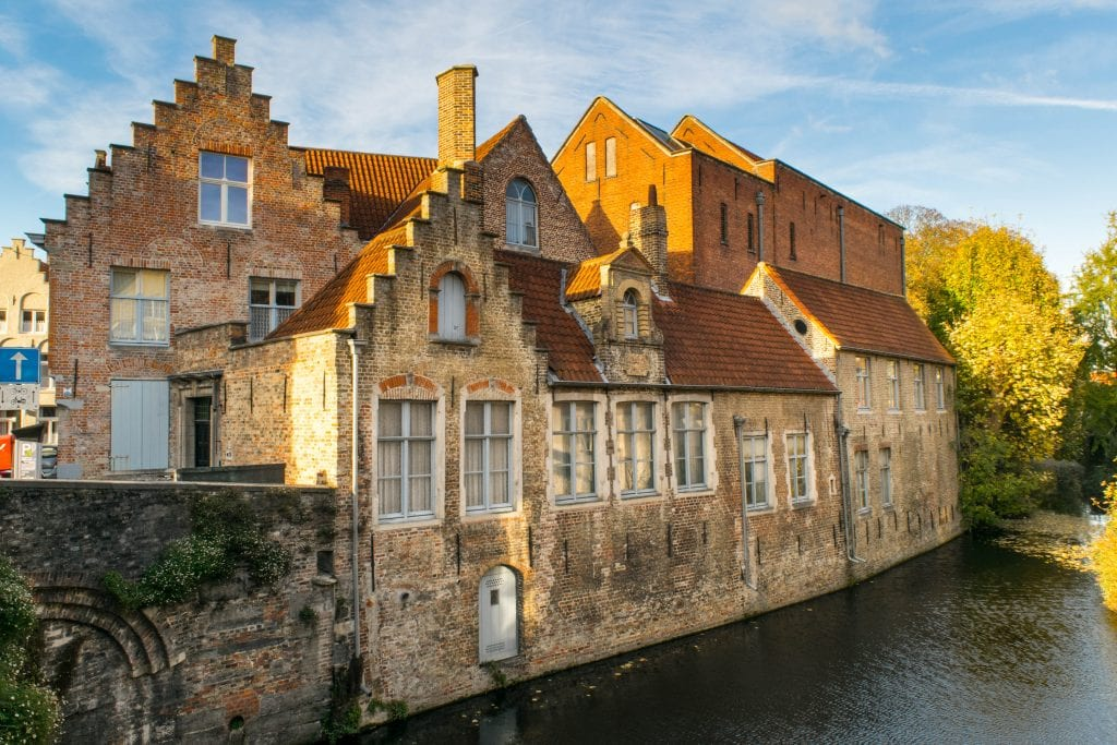 brick buildings along a small canal in bruges. canals are a popular reason to visit both ghent and bruges
