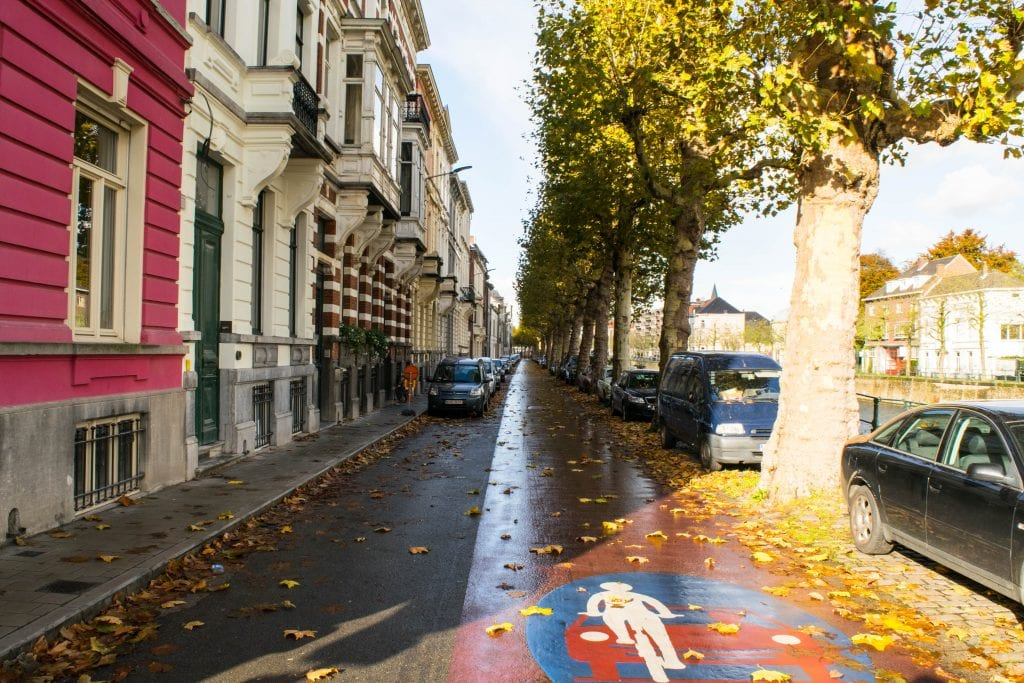 Empty street in Ghent Belgium with a few cars visible in the distance and yellow leaves on the ground--keep this damp weather in mind when making a fall packing list for Europe!