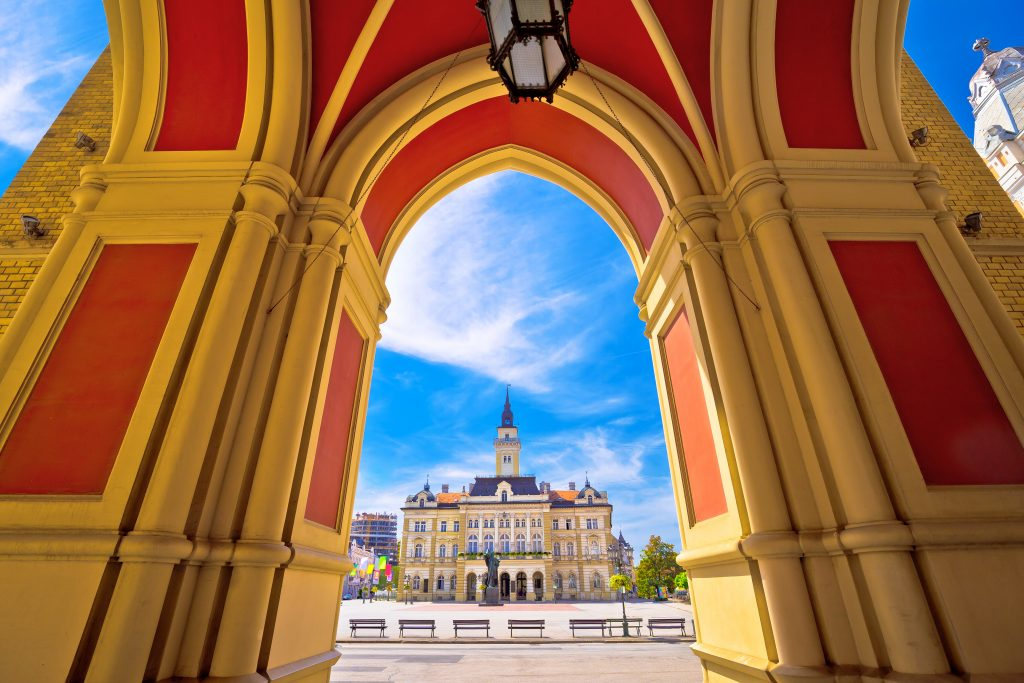 view of freedom square in novi sad serbia as seen through colorful red and yellow arches novi sad is one of the cheapest european cities to visit