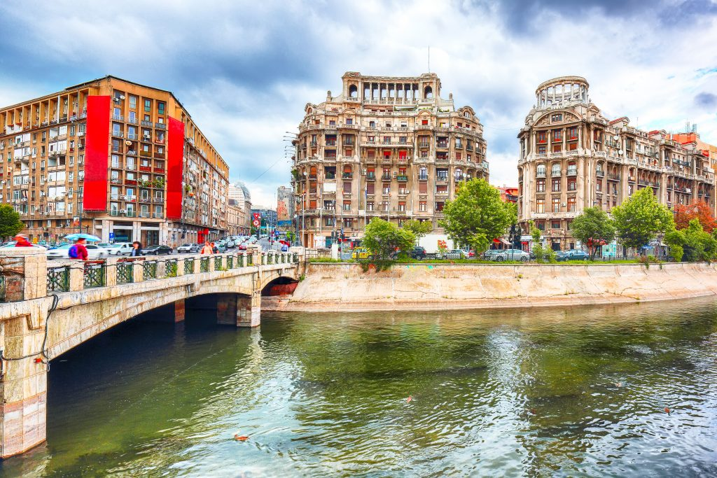 view of historic buildings in bucharest romania from across the river with a bridge in the left foreground