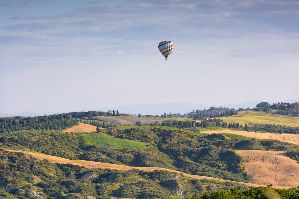 hot air balloon in the distance over the tuscany countyside, a bucket list tuscany travel experience