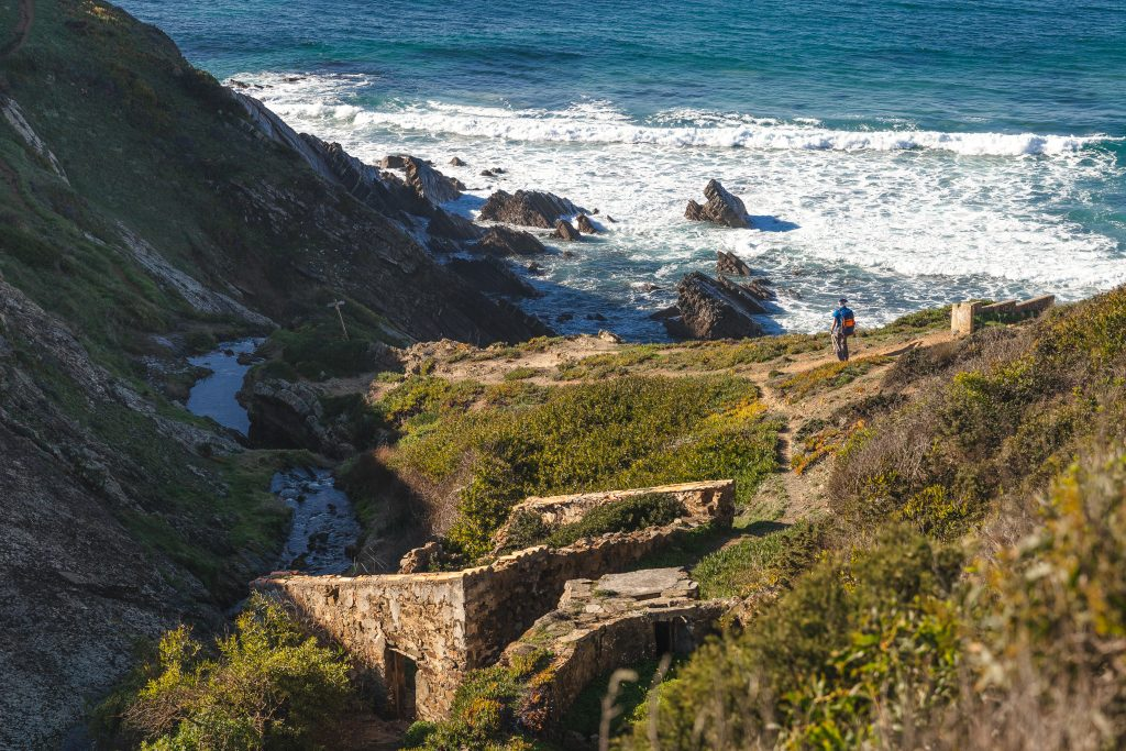 man hiking along the rugged fishermans trail on a rural section of the algarve, an offbeat european destination to visit