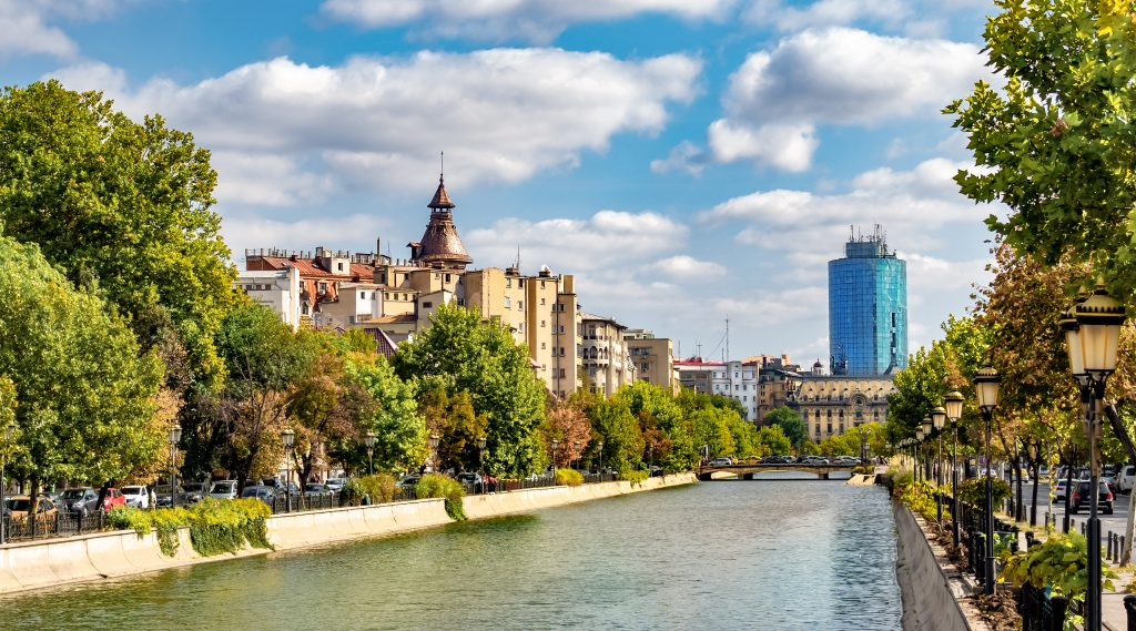 view of bucharest skyline with the river in the foreground, near many of the best things to do in bucharest romania