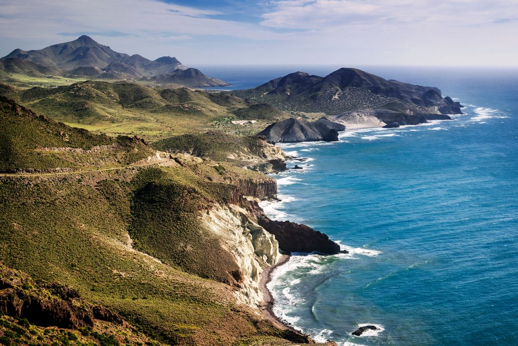 rugged landscape of cabo de gata natural park in spain, one of the best offbeat europe destinations to visit. water is to the right of the photo