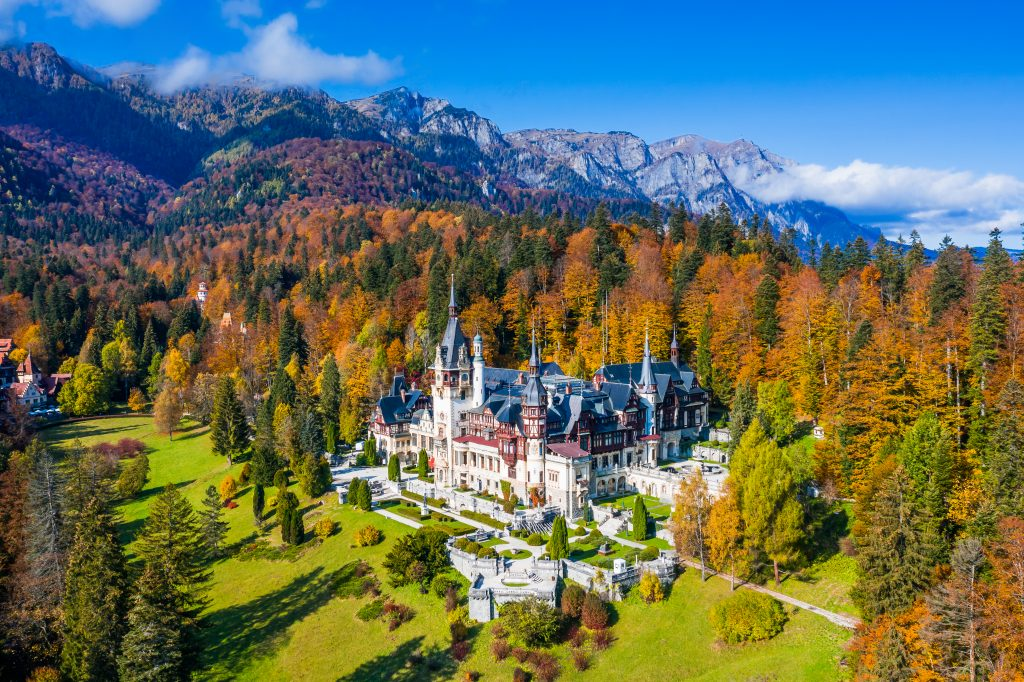 aerial view of peles castle romania with fall foliage surrounding it
