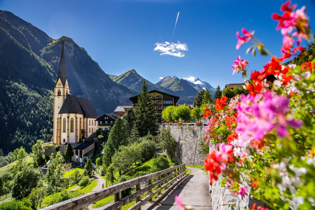 st vincent church with pink flowers blooming to the right Heiligenblut, Austria, one of the best offbeat places in europe