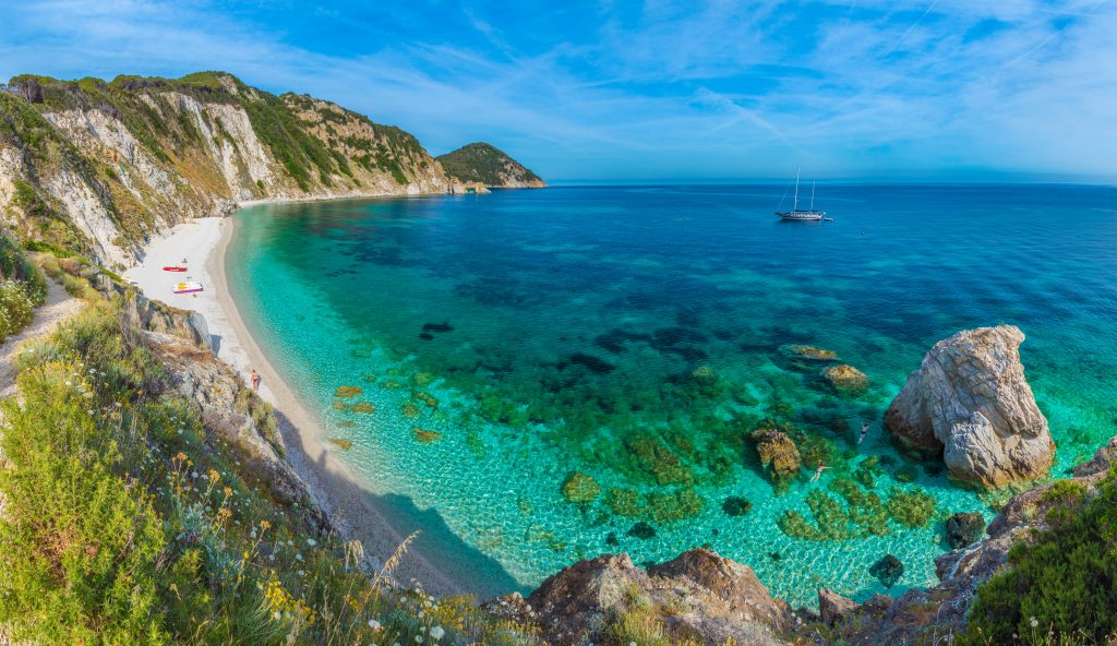 bright turquoise beach with land visible to the left on elba island, one of the best places to visit in tuscany italy