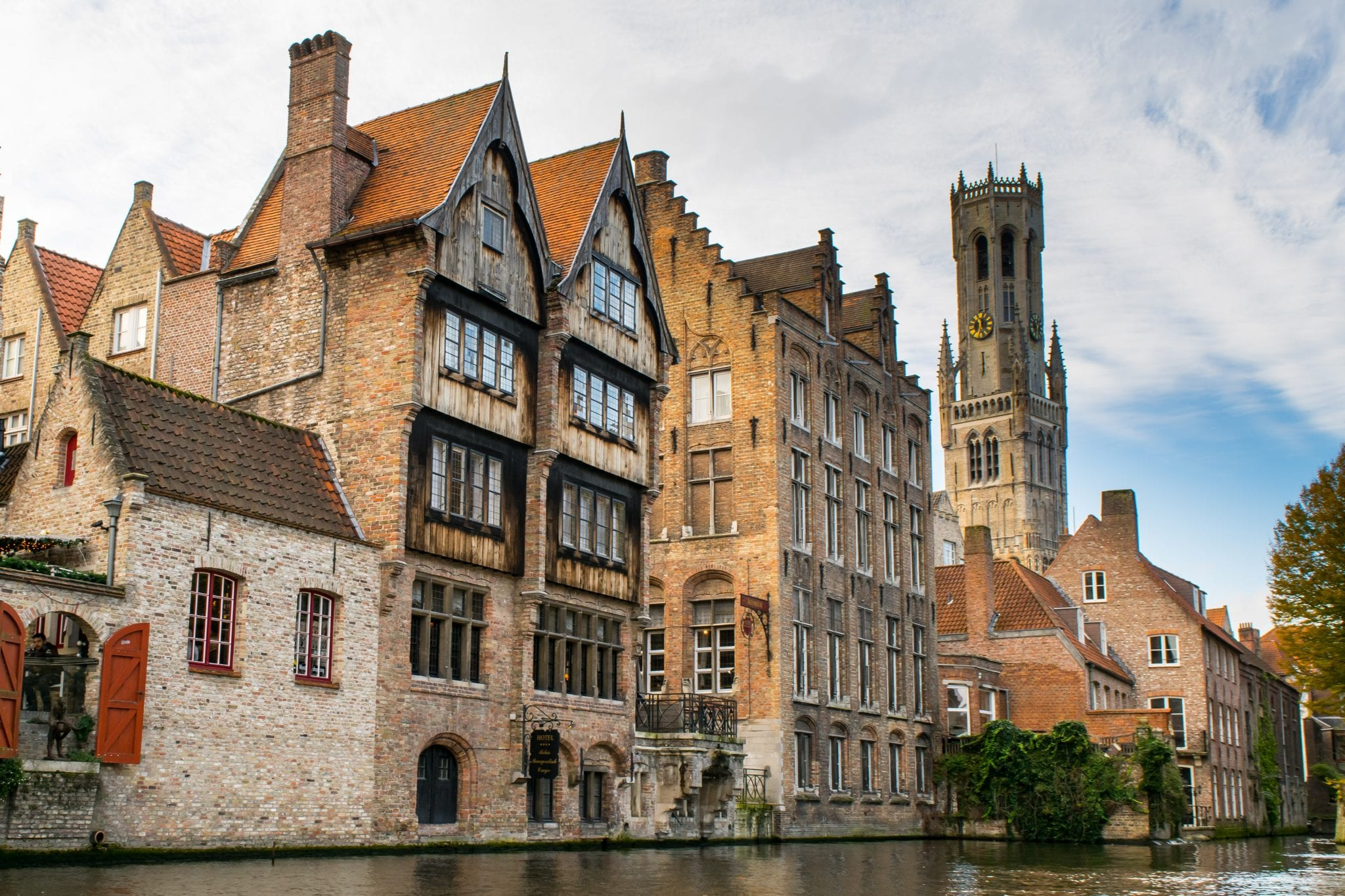 view of a wooden building along a canal in bruges belgium. canals are a big draw of bruges or ghent belgium
