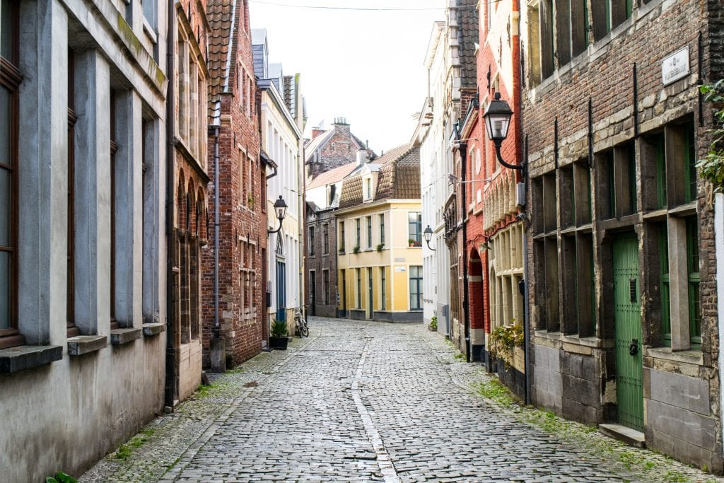 traditional flemish buildings lining an empty cobblestone street in patershol ghent