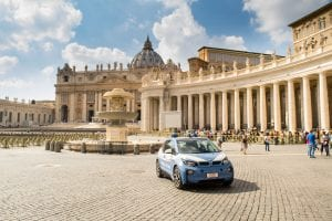 St Peter's Square on sunny day with car parked in the square--checking out this square is a must-see when touring Vatican City!
