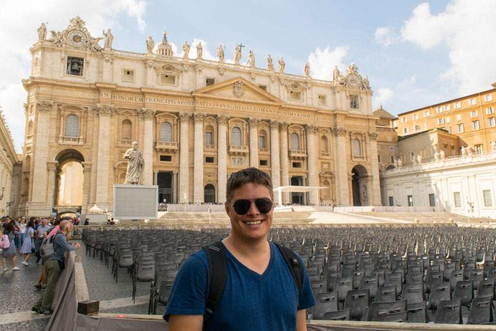 Jeremy Storm wearing aviator sunglasses standing in front of St Peter's Basilica when visiting Vatican City Rome