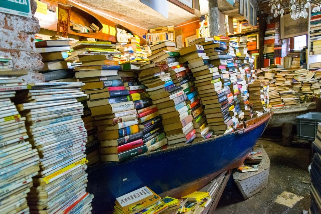 Canoe full of stacks of books in Libreria Acqua Alta Venezia