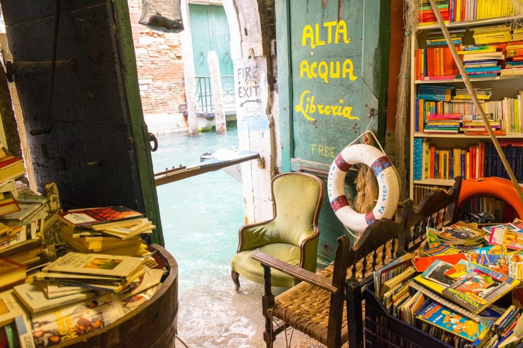 Libreria Acqua Alta Venezia: fire exit during minor acqua alta, there's water visible near the legs of the green chair.