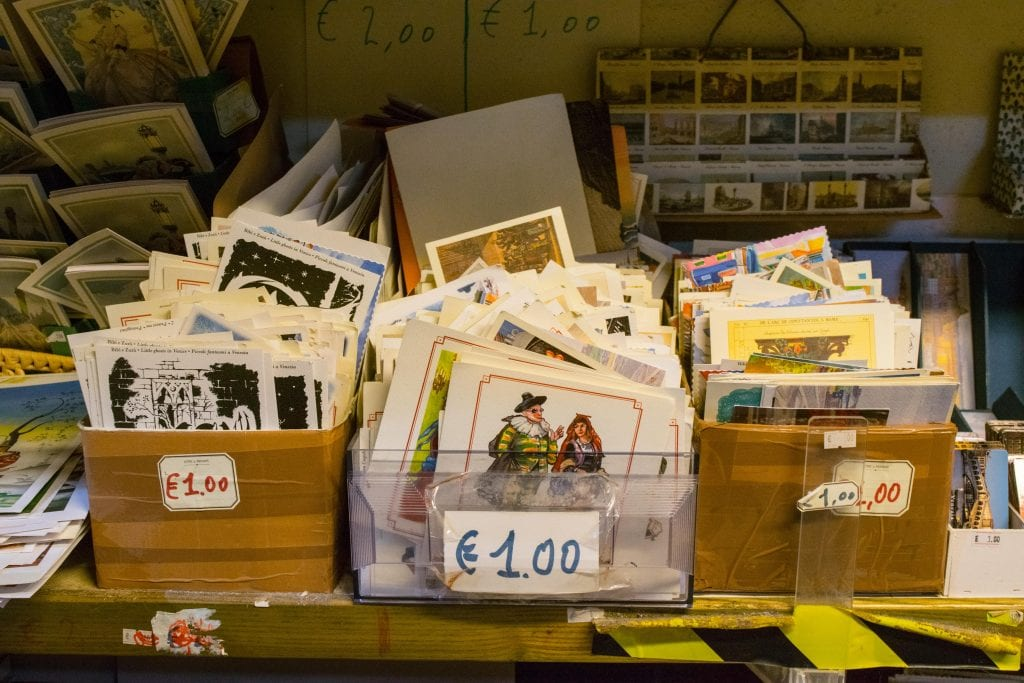 Pile of postcards for sale at Libreria Acqua Alta Venice. Bins are marked with 1 Euro price tag.