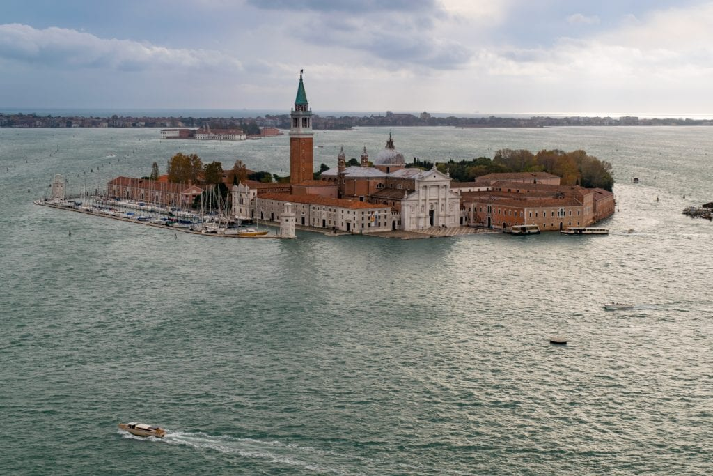 Photo of San Giorgio Maggiore from above surrounded by the Venetian Lagoon--this small island is home to one of the best views in Venice!