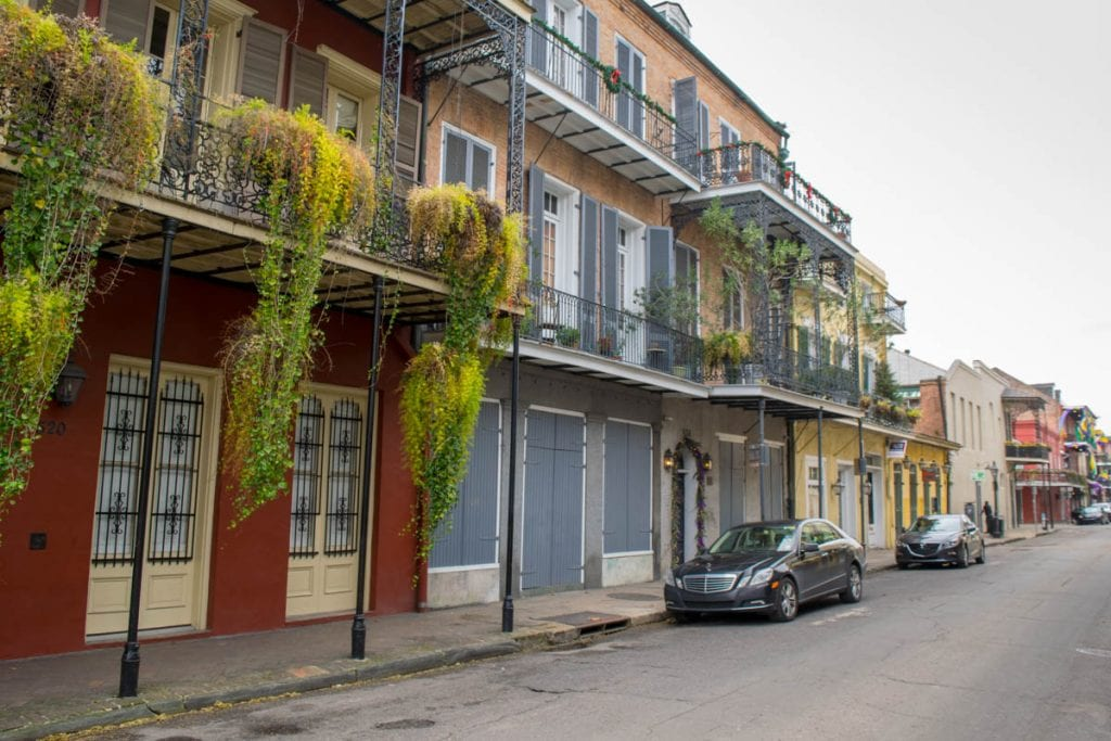 Photo of a street in the French Quarter of New Orleans--a neighborhood which has definitely inspired plenty of New Orleans quotes! There are red and blue buildings on the left, and plants hanging from the balcony.