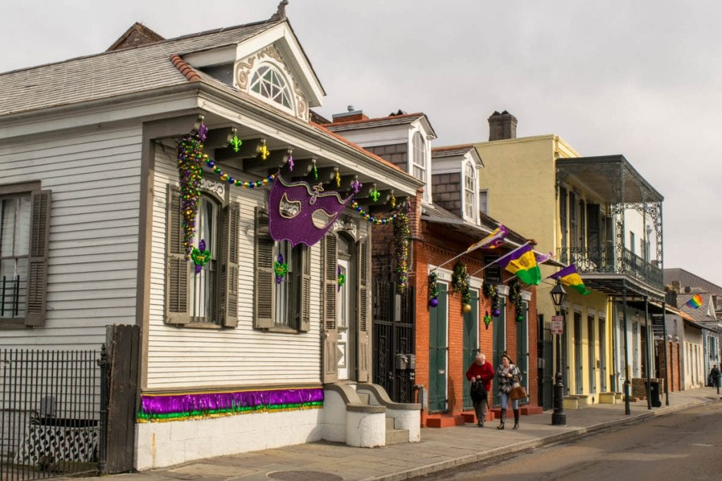 Row of colorful houses in New Orleans French Quarter with Mardi Gras decorations out front, as seen during a long weekend in New Orleans vacation.