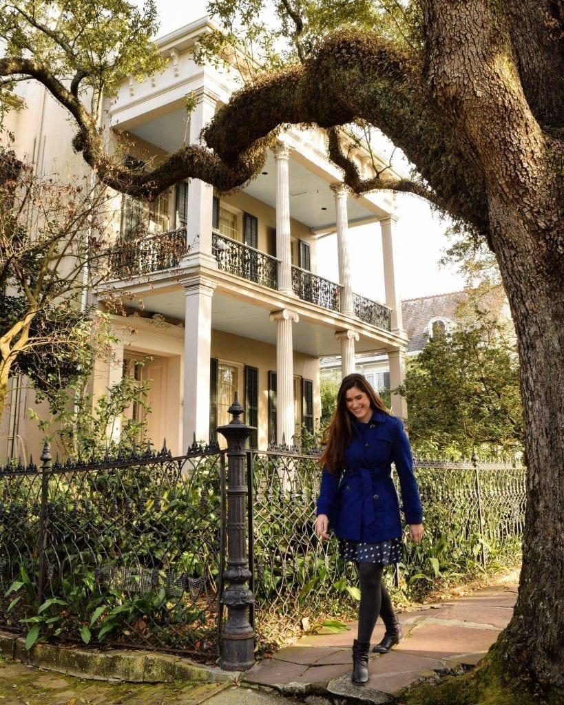 Kate Storm in a blue coat walking in front of a mansion and below a large oak tree in the Garden District during 3 days in NOLA