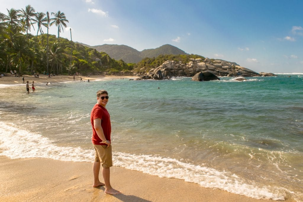 Jeremy Storm in a red shirt standing next to the water at Cabo San Juan Beach in Tayrona National Park. We definitely recommend seeing this beach as part of your 14 days in Colombia itinerary!