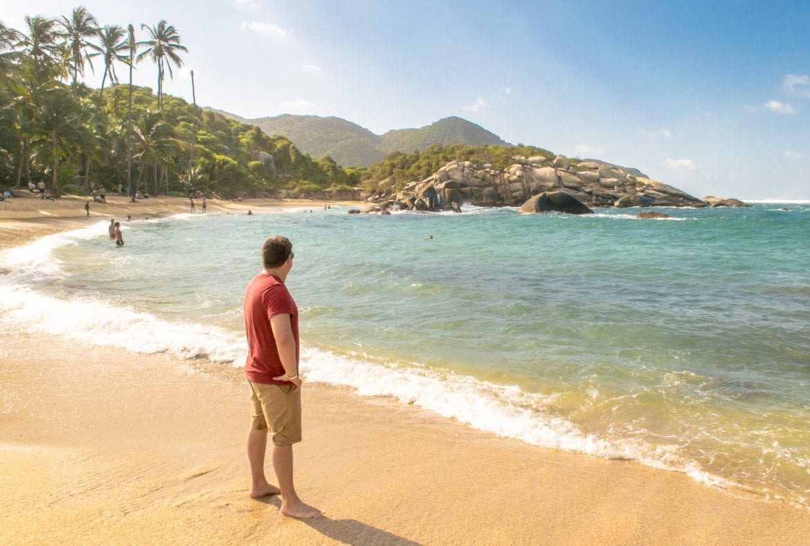 Jeremy Storm in a red shirt standing on a beach in Tayrona National Park Colombia--be sure to go through this international travel checklist before heading off to gorgeous spots like this!