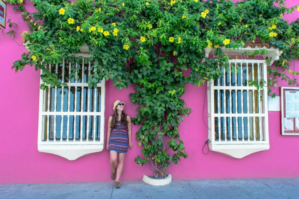 Kate Storm standing in a colorful dress against a bright pink wall in Cartagena--you'll want lots of light, colorful dresses like this on your packing list for Colombia