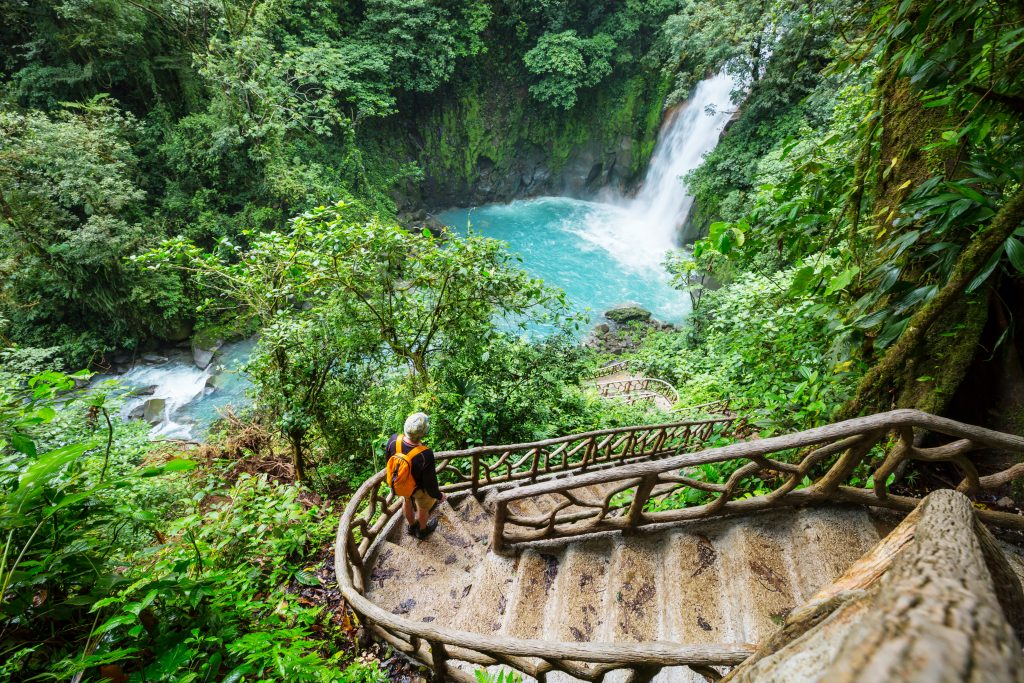 woman walking down a staircase to a waterfall in costa rica