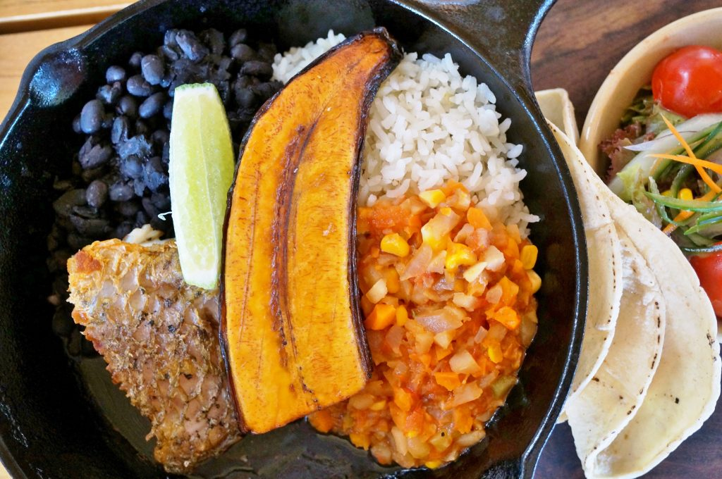 typical costa rican meal on a black plate as seen from above. when deciding costa rica vs nicaragua, the food isn't a deciding factor