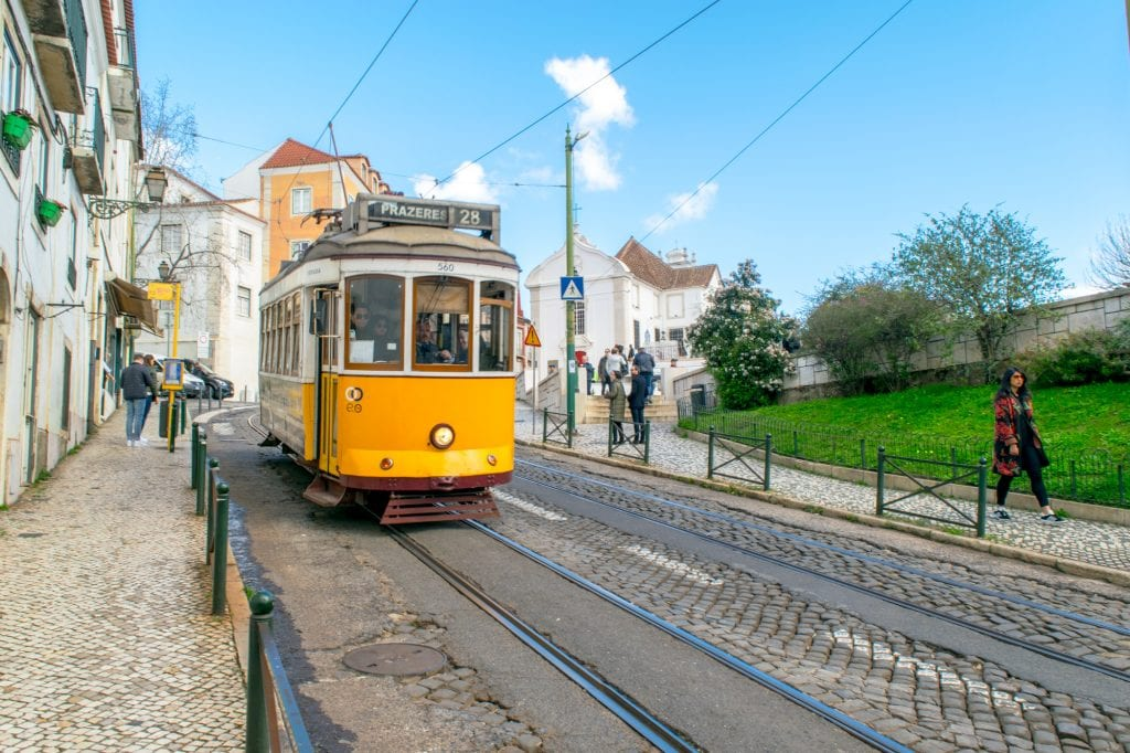 Bright yellow tram ascending a hill in Lisbon Portugal on a sunny day--be sure to take plenty of pretty tram photos during your one day in Lisbon!