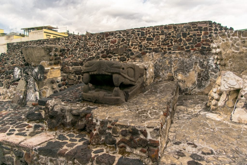 statue of a snake head at templo mayor in the heart of mexico city